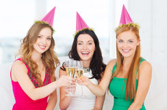 Three women wearing hats with champagne glasses Royalty Free Stock Image