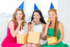Three women wearing hats with gifts blowing horns Stock Photos