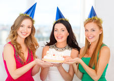 Three women wearing hats holding cake with candles Royalty Free Stock Images