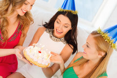 Three women wearing hats holding cake with candles. Celebration, food, friends, bachelorette party, birthday concept - three smiling women wearing blue hats Royalty Free Stock Photo