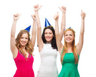 Three women wearing hats and showing thumbs up Royalty Free Stock Photos