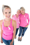 Three women wearing pink tops and breast cancer ribbons Royalty Free Stock Images