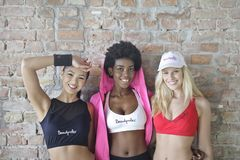 Three Women Wearing Sport Bra Standing Behind Concrete Wall Stock Photography