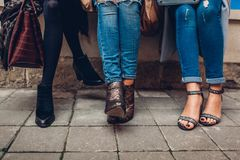 Three women wearing stylish shoes and accessories outdoors. Beauty fashion concept stock photography