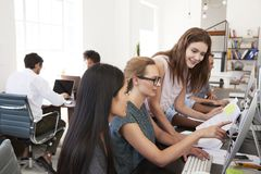 Three women working together at computer in open plan office Stock Images