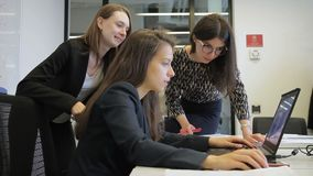 Three women is working using laptop in large company. Young brunette sits at table and looks attentively at screen of black pc, talking to female colleagues stock footage