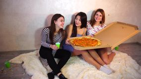 Cute girls cool spend time and enjoy pizza, sit on floor in bright bedroom in evening. stock video