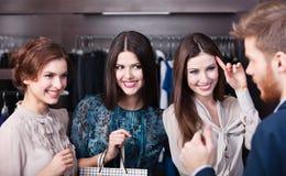 Three wonderful women talk with salesperson. Three wonderful women flirt with salesperson stock photography