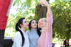 Three wonderful young girl girlfriends make selfie, photo on pho Royalty Free Stock Images