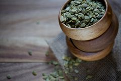 Three wood bowls stacked with pumpkin seeds on wood board Royalty Free Stock Images