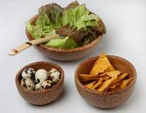Three wooden bowls with fresh green salad, quail e Royalty Free Stock Image