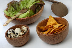 Three wooden bowls with fresh green salad, quail e Stock Image