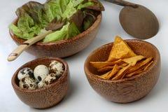Three wooden bowls with fresh green salad, quail e Stock Image