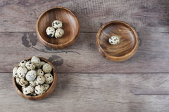 Three wooden bowls with quail eggs. Rustic wood background, diffused natural light. A different type of concept image stock photos