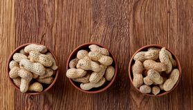 Three wooden bowls of unpeeled peanuts over rustic wooden background closeup, selective focus. Some copy space for your text. Healthful and nutritious snack royalty free stock photo