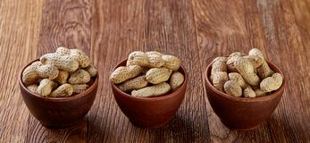 Three wooden bowls of unpeeled peanuts over rustic wooden background closeup, selective focus. Some copy space for your text. Healthful and nutritious snack stock image
