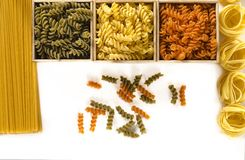 Three wooden boxes with colored fusilli are on a white background next to spaghetti and tagliatelle stock photos