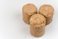 Three wooden briquettes made of pressed sawdust Stock Photography