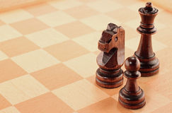 Three Wooden Chess Pieces on a Chessboard Stock Images