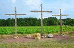 Three Wooden Christian Crosses. Sitting on a small hill in a field with rocks around the base of each cross and Christmas lights wrapped around each cross Stock Photography