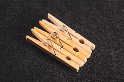 Three wooden clothespin clamps. On a dark textured background Stock Photos