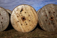 Three wooden coils for electric cables, stored outdoors. Three wooden grunge coil surfaces for electric cables outdoors in a field under a blue sky Stock Photos