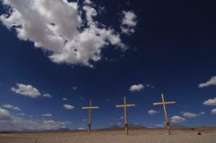 Three wooden crosses in desert with blue sky. Three yellow wooden crosses in barren desert with blue sky background Royalty Free Stock Photo