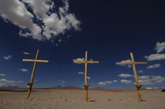 Three wooden crosses in desert with blue sky. Three yellow wooden crosses in barren desert with blue sky background Stock Image