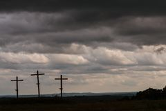 Three Wooden Crosses Stand Against Dark Ominous Storm Clouds. Three crosses in a North Georgia field stand against a dark, ominous sky Stock Photo