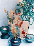 Three wooden deer in the form of a family, decorated with garlands, decorative tree with lights in turquoise colors royalty free stock image