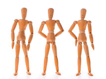 Three wooden dolls in different poses royalty free stock image