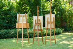 Three wooden easels with paintings standing on a green lawn in a garden or park in a concept of art and nature. royalty free stock image