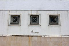 Wooden frame windows with rusted rectangle bars mounted on dilapidated wall. Three wooden frame rectangle glass windows with partially rusted metal bars mounted Stock Photography
