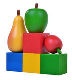 Three wooden fruits on colored cubes Stock Photos