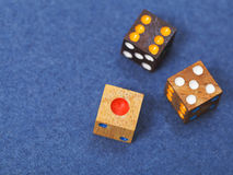 Three wooden gambling dices on blue cloth Royalty Free Stock Image