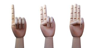 Three wooden hands, with one, two and three fingers raised respectively. Isolated on white background Royalty Free Stock Image