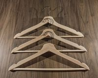 Three wooden hangers on darker wood background stock photo