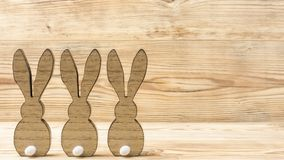 Three wooden hares. In front of a wood background Stock Photo
