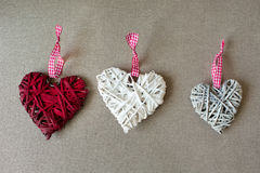 Three wooden heart shapes on linen fabric. Stock Photo