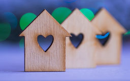 Three wooden houses with hole in form of heart on colorful bokeh Royalty Free Stock Photos