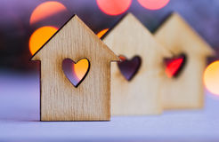 Three wooden houses with hole in form of heart on colorful bokeh Stock Photos