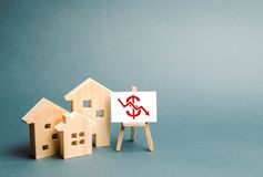 Free Three Wooden Houses With A Stand With Red Dollar Sign And Arrow Down. Concept Of Real Estate Value Decrease. Low Liquidity Royalty Free Stock Image - 156037676