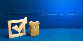 Three wooden human figures stand together next to a tick in the box. The concept of elections and social technologies. Volunteers stock photography