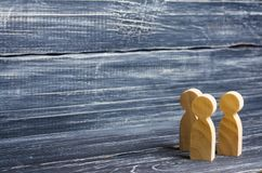 Three wooden human figures stand together. Social concept royalty free stock photos