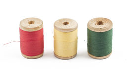 Three wooden multicolored thread coils on white. Background (red, yellow and green Stock Image