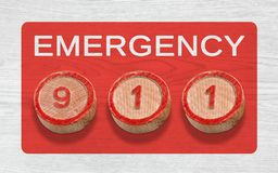 Three Wooden Pieces Depicting 911 Emergency Number. Three cylinder-shaped wooden pieces on a white wood background depicting the 911 emergency number Stock Photos