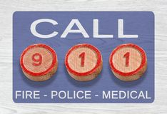 Three Wooden Pieces Depicting 911 Emergency Number. Three cylinder-shaped wooden pieces on a white wood background depicting the 911 emergency number Stock Image