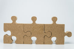 Three Wooden pieces of jigsaw puzzle with white background and selective focus Stock Image