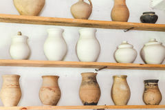 Three wooden shelves with jars of different shapes Royalty Free Stock Photo