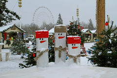 Three wooden snowmen in snow on the background of `Christmas light` festival in VDNKh in Moscow Stock Photo